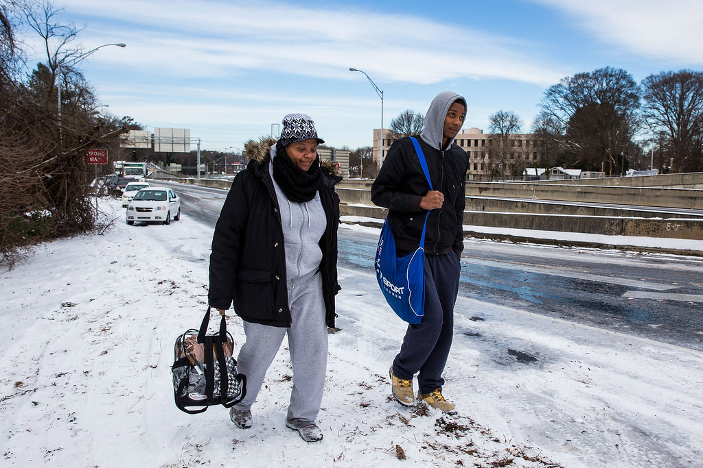 . North Atlanta High School student David Hunter and his mother Demetra Dobbins walk up an exit ramp along I-75 North on their way home during the winter storm January 29, 2014 in Atlanta, Georgia.  (Photo by Daniel Shirey/Getty Images)