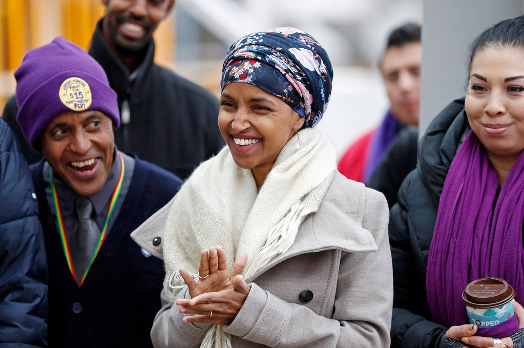 . Ilhan Omar, center, the first Somali-American elected to a state legislature, applauds during a rally Tuesday, Nov. 29, 2016, at the Minneapolis-St. Paul International Airport in Minneapolis, in support of efforts calling for $15 minimum wages. Those in attendance included airport workers. (AP Photo/Jim Mone)