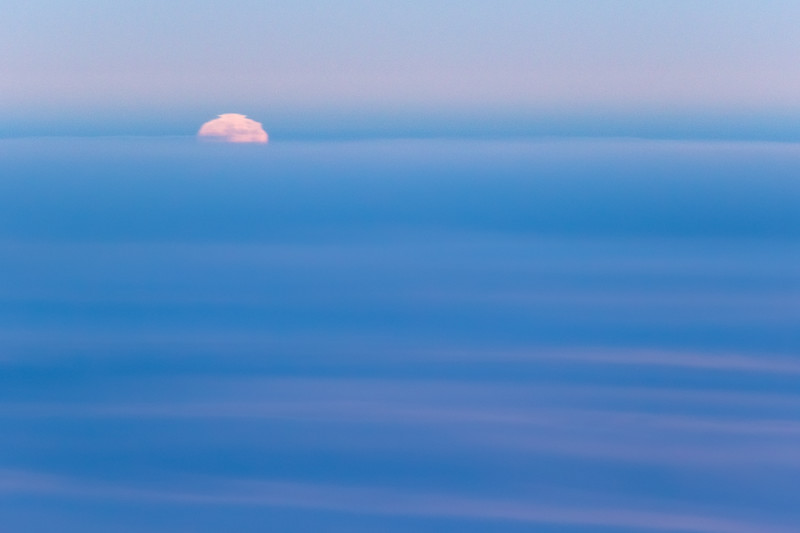 Close view of a warped full moon rising above blue clouds at sunset from an airplane