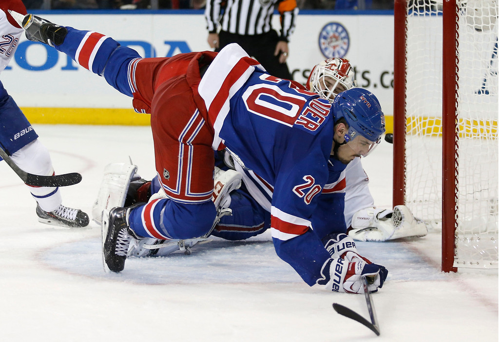 . New York Rangers left wing Chris Kreider (20) flies in front of Montreal Canadiens goalie Dustin Tokarski (35) as the puck sails past the far post during the second period of Game 3 of the NHL hockey Stanley Cup playoffs Eastern Conference finals, Thursday, May 22, 2014, in New York. (AP Photo/Kathy Willens)