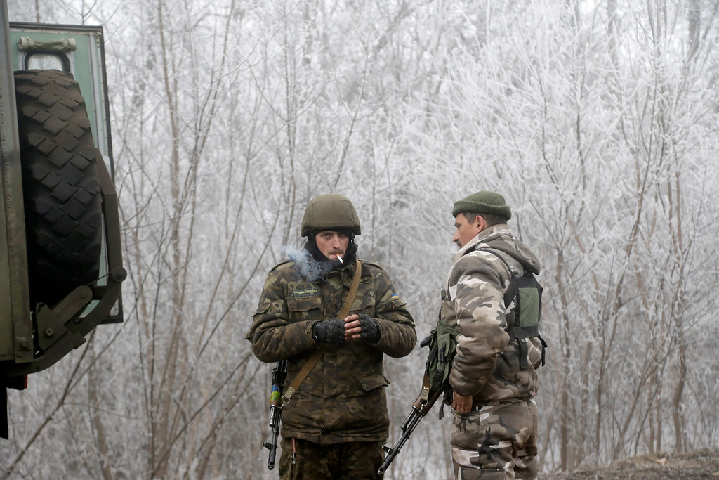 . Ukrainian government soldiers take a rest on the road between the towns of Dabeltseve and Artemivsk, Ukraine, Sunday, Feb. 15, 2015. International attention will be focused in the coming days on the strategic railway hub of Debaltseve, where Ukrainian government forces have for weeks been fending off severe onslaughts from pro-Russian separatists. A cease-fire was declared in eastern Ukraine, kindling slender hopes of a reprieve from a conflict that has claimed more than 5,300 lives. (AP Photo/Petr David Josek)