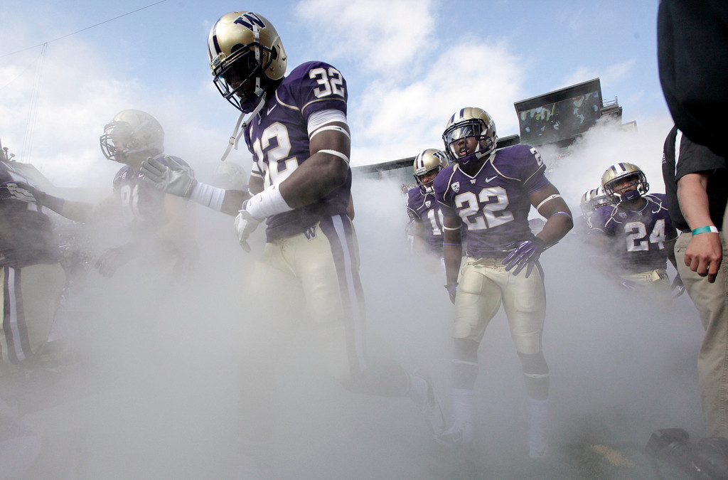 . Washington players run  onto the field before an NCAA college football game against Idaho State on Saturday, Sept. 21, 2013, in Seattle. Washington won 56-0. (AP Photo/Elaine Thompson)