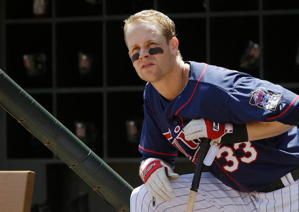 . The Twins\' Justin Morneau, the subject of recent trade rumors, waits his turn to bat in the first inning of their game against the Cleveland Indians, Sunday, July 21, 2013 in Minneapolis. (AP Photo/Jim Mone)