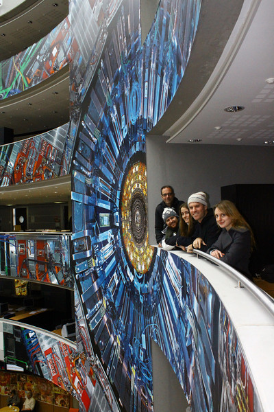 The whole film crew beside an actual 1:1 size photograph of the CMS detector inside the Large Hadron Collider. Michael Hoch, the working physicist and unofficial in-house artist for CERN who created this life size photograph of the detector, also took this photo of us next to it.  From left to right:  Ben Eshbach, David Marks, Marie Mart Roijackers, Steve Elkins, Becky Calinsky