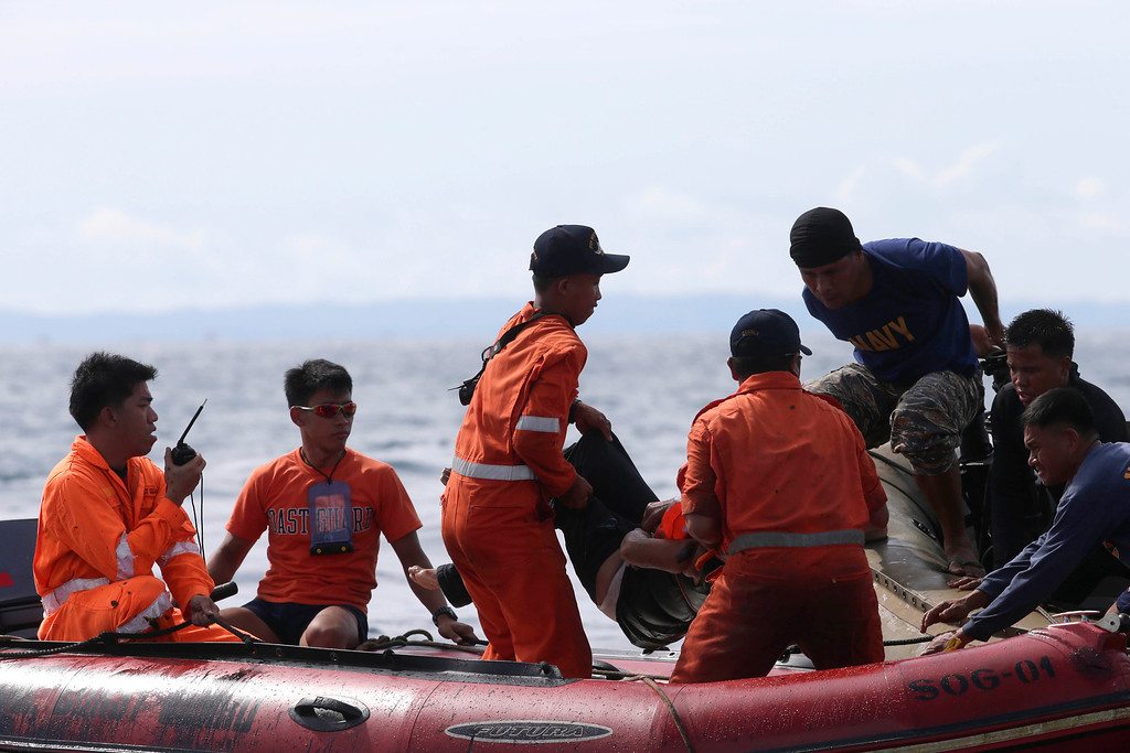 . Philippine Navy and Coast Guard divers retrieve a body from the waters off the coast of Talisay city, Cebu province a day after a passenger ferry MV Thomas of Aquinas collided with a cargo ship Sulpicio Express Siete in central Philippines Saturday Aug. 17, 2013. Divers combed through a sunken ferry Saturday to retrieve the bodies of more than 200 people still missing from an overnight collision with a cargo vessel near the central Philippine port of Cebu that sent passengers jumping into the ocean and leaving many others trapped. At least 28 were confirmed dead and hundreds rescued. The captain of the ferry MV Thomas Aquinas, which was approaching the port late Friday, ordered the ship abandoned when it began listing and then sank just minutes after collision with the MV Sulpicio Express, coast guard deputy chief Rear Adm. Luis Tuason said. (AP Photo/Bullit Marquez)