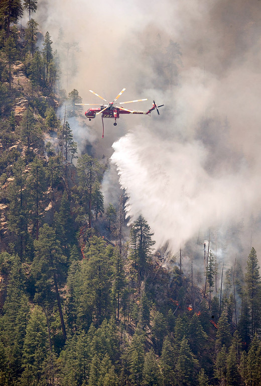 . Helicopters drop water on part of the Slide Fire in Sterling Canyon at the Oak Creek Overlook above Sedona, Ariz. on Thursday, May 22, 2014. Hundreds of firefighters worked Thursday to protect communities on the edge of Flagstaff from a wildfire that is chewing up a scenic Arizona canyon with towering flames and burning entire trees down to nothing but ash. (AP Photo/The Arizona Republic, Michael Schennum)