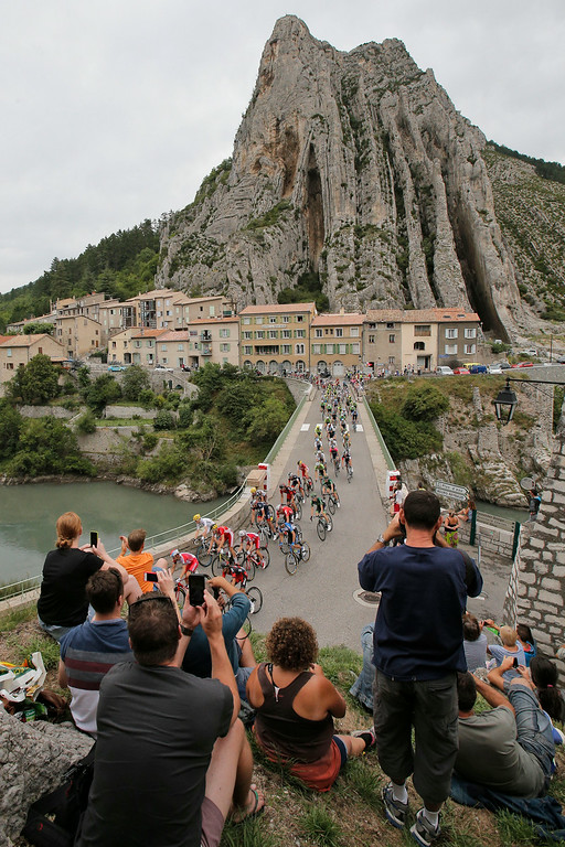 . The pack passes a bridge spanning Durance river in Sisteron during the fifteenth stage of the Tour de France cycling race over 222 kilometers (137.9 miles) with start in Tallard and finish in Nimes, France, Sunday, July 20, 2014. (AP Photo/Christophe Ena)