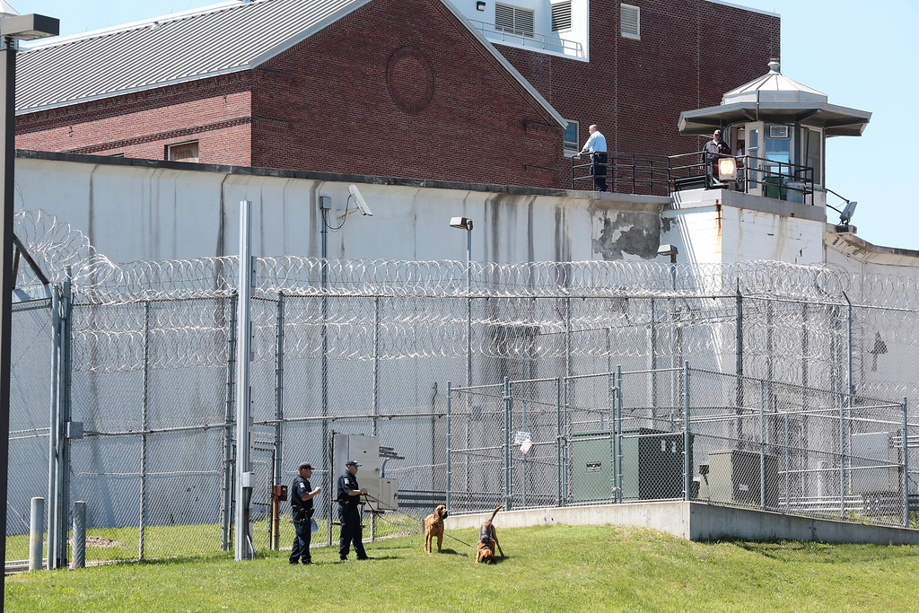 . Law enforcement officers with bloodhounds stand guard at one of the entrances to the Clinton Correctional Facility in Dannemora, N.Y. on Saturday, June 6, 2015. Two convicted murderers used power tools to cut through steel pipes at the maximum-security prison near the Canadian border and escaped through a manhole, Gov. Andrew Cuomo said Saturday. (Gabe Dickens/Press-Republican via AP)