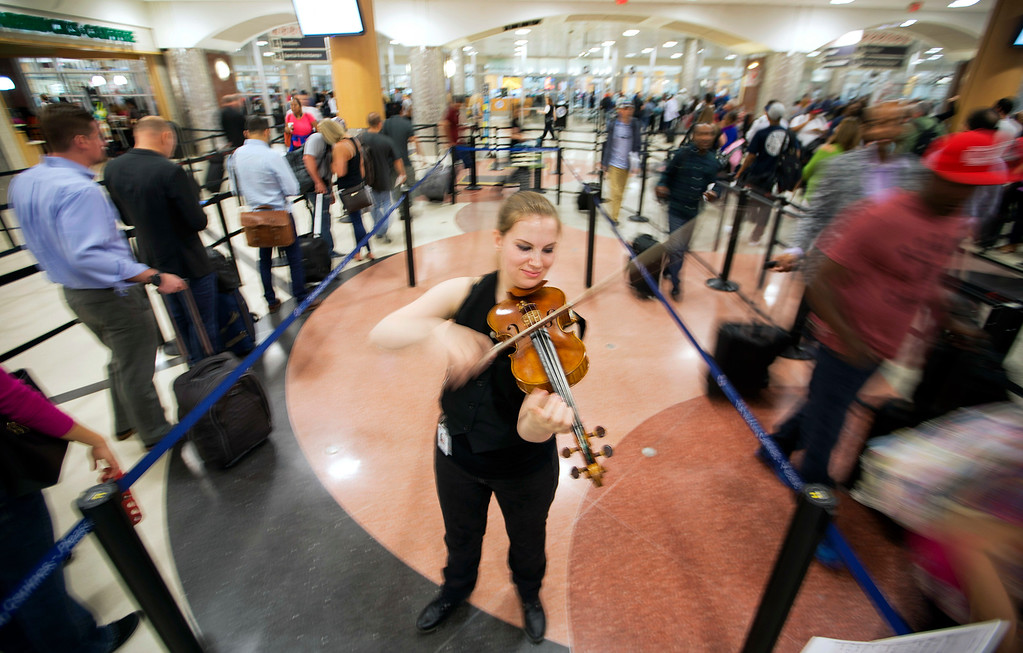 . In this image made with a slow shutter speed, violinist Jennifer Warrilow plays for travelers moving through a security checkpoint line at Hartsfield-Jackson Atlanta International Airport, Thursday, May 19, 2016, in Atlanta. The airlines have a message for fliers: Get to the airport early. Long lines at Transportation Security Administration checkpoints have plagued thousands of travelers this spring, causing many of them to miss flights. The situation is expected to get worse in the summer with an average of 2.5 million passengers a day flying. (AP Photo/David Goldman)