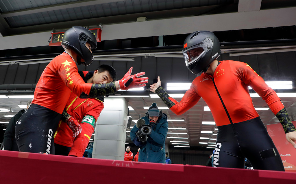 . Driver Jin Jian, right, and Shen Ke of China slap hands after the second run during the two-man bobsled competition at the 2018 Winter Olympics in Pyeongchang, South Korea, Sunday, Feb. 18, 2018. (AP Photo/Michael Sohn)