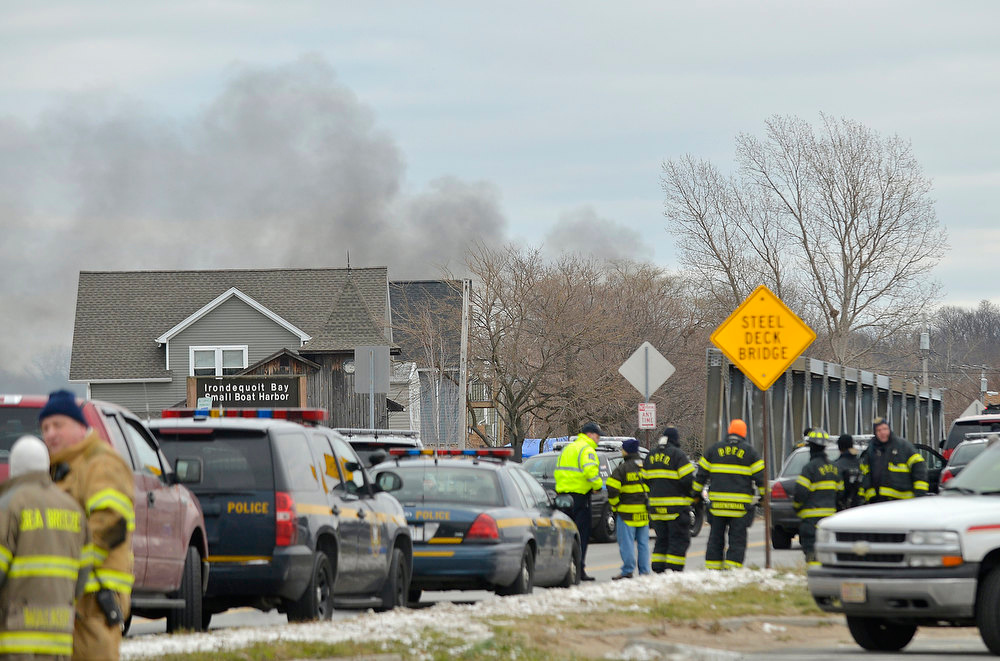 . Smoke is seen from the site of a fire in Webster, N.Y., Monday, Dec. 24, 2012. Police in New York state say a man who killed two firefighters in a Christmas Eve ambush had served 17 years for manslaughter in the death of his grandmother.  (AP Photo/Seth Binnix)