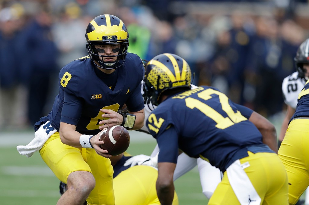 . Michigan quarterback John O\'Korn hands off to running back Chris Evans (12) during the first half of an NCAA college football game against Ohio State, Saturday, Nov. 25, 2017, in Ann Arbor, Mich. (AP Photo/Carlos Osorio)