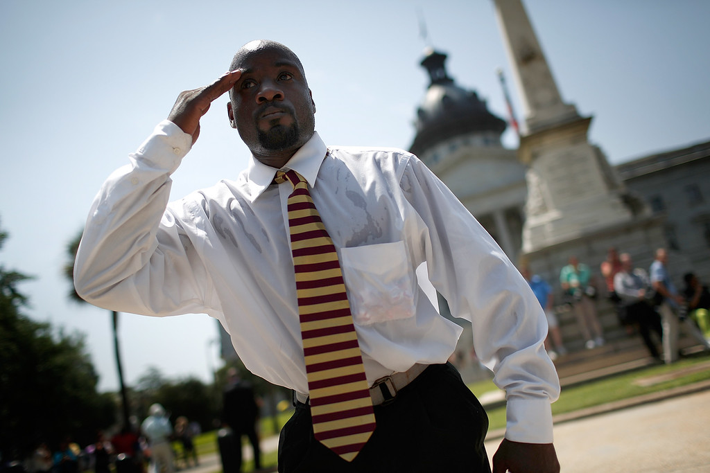. A man salutes as the procession carrying the casket of Rev. Clementa Pinckney moves down Main Street at the South Carolina State House June 24, 2015 in Columbia, South Carolina. Pinckney was one of nine people killed during a Bible study inside Emanuel AME church in Charleston. U.S. President Barack Obama and Vice President Joe Biden are expected to attend the funeral which is set for Friday June 26 at the TD Arena.  (Photo by Joe Raedle/Getty Images)