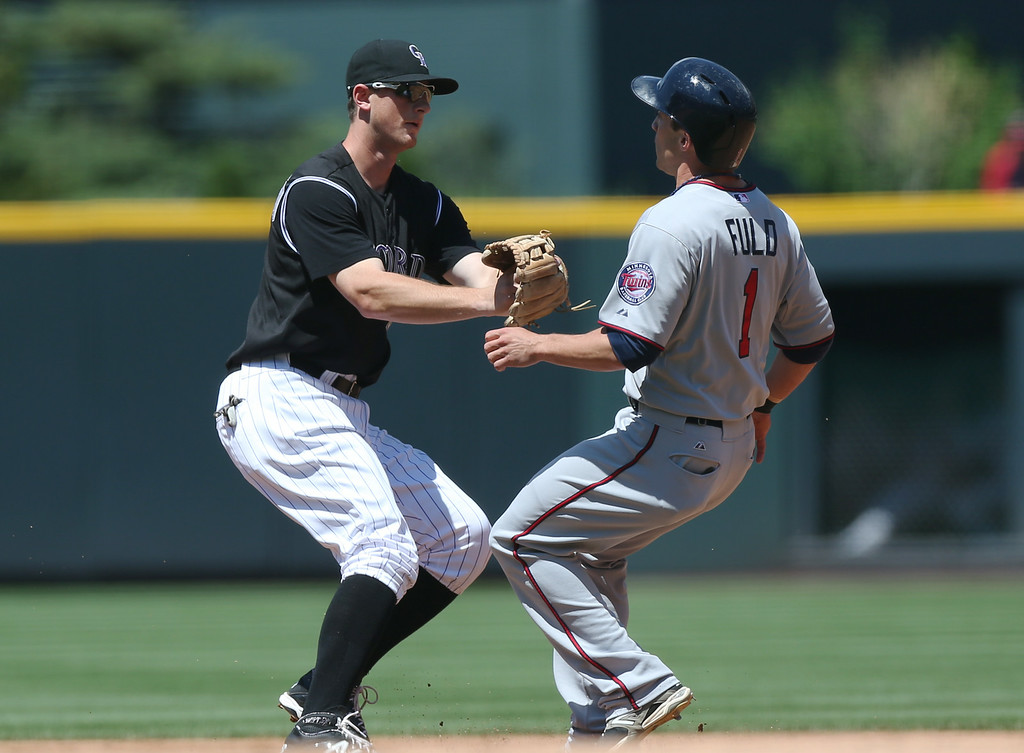 . Colorado Rockies second baseman DJ LeMahieu, left, tags out Minnesota Twins\' Sam Fuld as he tries to advance from first to second base in the first inning. (AP Photo/David Zalubowski)