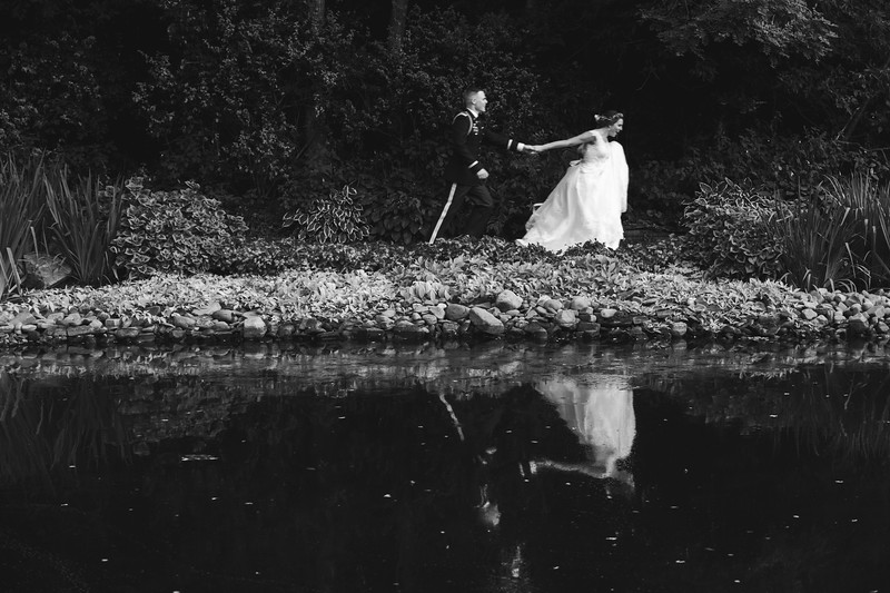 The bride leads the groom by the hand as she runs along the bank of the reflecting pond.