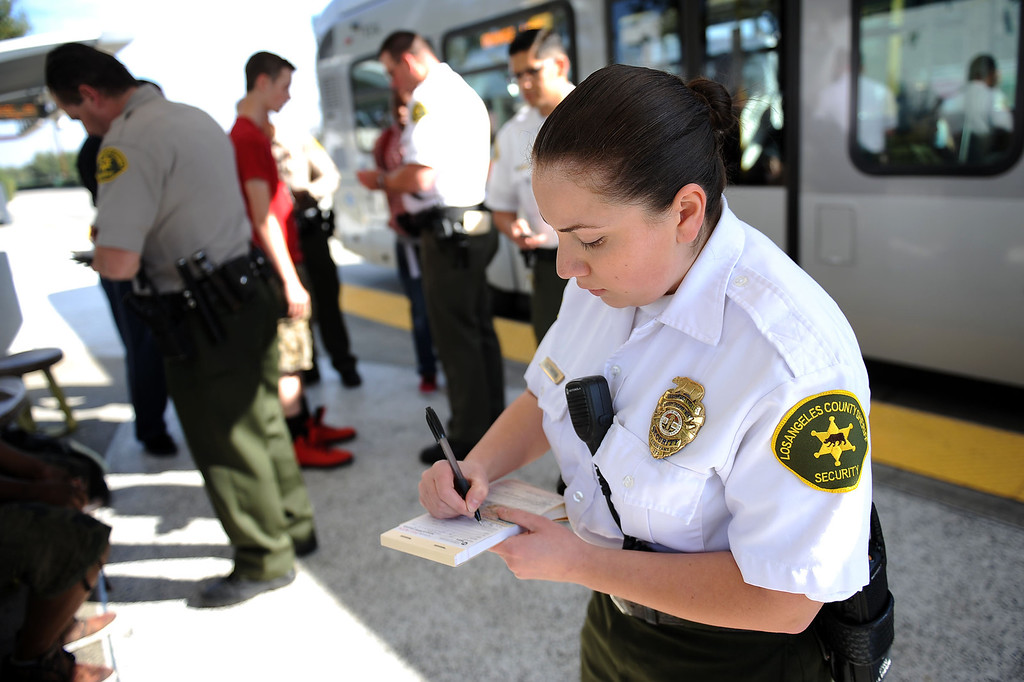 . LA County Sheriff security assistant Vardui Sultanyan cites a bus rider for fare evasion during an Orange Line fare enforcement operation at the Van Nuys Orange Line Station February 25, 2014.  Officials from Metro and the Los Angeles Sheriff\'s Department Transit Services Bureau announced a new two-pronged effort to cut down on fare-evaders on the Orange Line by improving communications and beefing up enforcement.(Andy Holzman/Los Angeles Daily News)