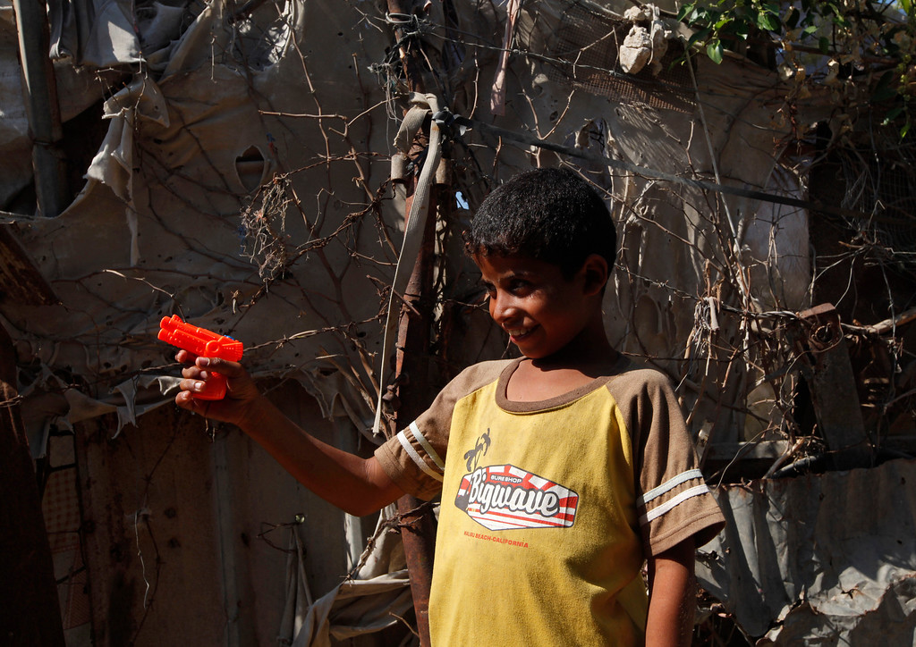 . In this Thursday, Oct. 17, 2013 photo, Mohammed Alwadiya, 11, plays with a toy gun while celebrating on the third day of the Muslim festival of Eid al-Adha in front of his family\'s house in Gaza City. The Alwadiya family is among the some 45 percent of Gazans who live in dire poverty, defined by the United Nations as living on less than $2 a day. Most of the family\'s clothes and food comes from donations.   (AP Photo/Adel Hana)