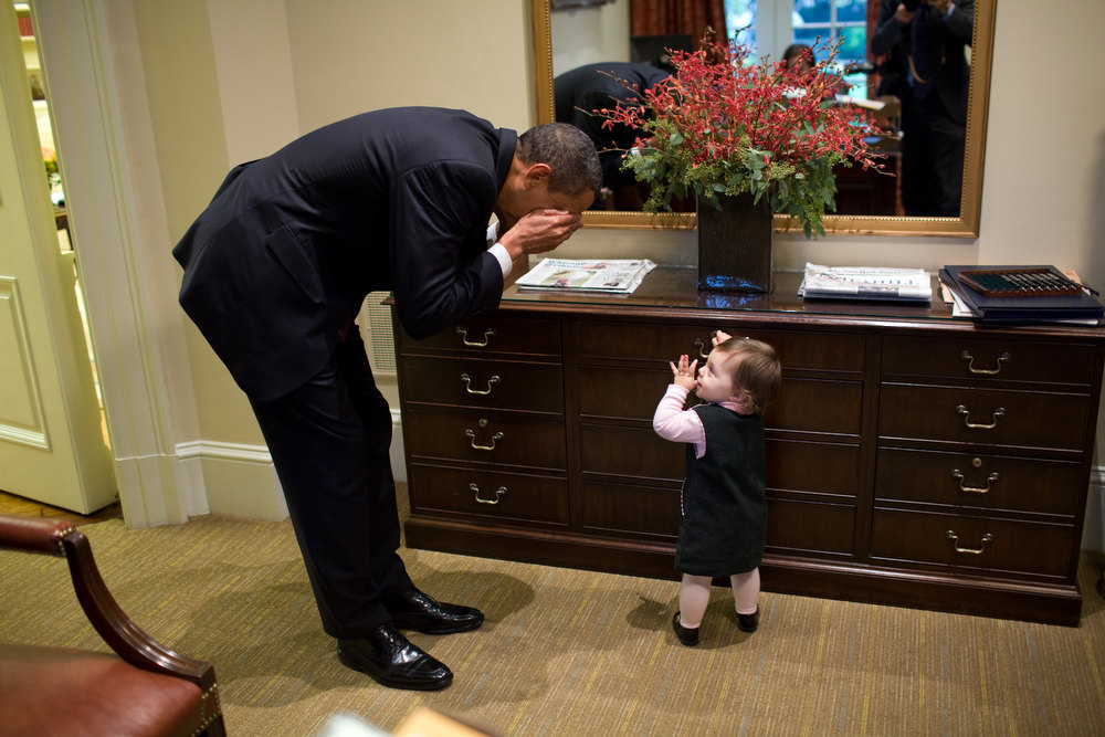 "Description of . Oct. 30, 2009 ""The President plays peek-a-boo with the daughter of White House staffer Emmitt Beliveau in the Outer Oval Office. It's interesting to note that this photograph was taken not long after the conclusion of his Afghanistan meeting in the Situation Room. So he went from this very substantive meeting to being able to lighten up for a minute with this young girl."" (Official White House photo by Pete Souza)"