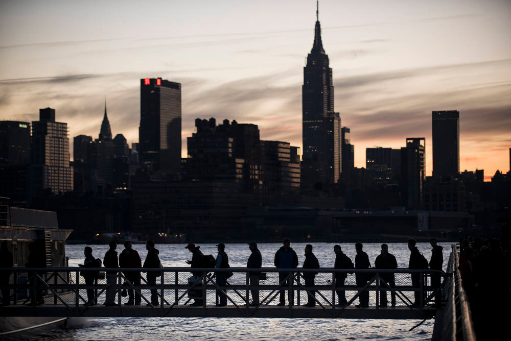 Description of . People board the NY Waterways ferry with the Manhattan skyline in the background November 1, 2012 in Hoboken, New Jersey. Hurricane Sandy, which made landfall along the New Jersey shore, left parts of the state and the surrounding area without power including much of lower Manhattan south of 34th Street. AFP PHOTO/Brendan  SMIALOWSKI/AFP/Getty Images