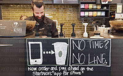 A Starbucks barista partner works behind a Starbucks app sign in Seattle, Washington
