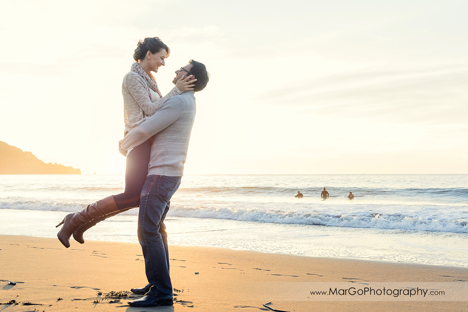 man lifting woman in grey sweater and jeans with ocean in background during engagement session at San Francisco Baker Beach