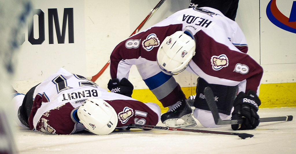 . Colorado defenseman Andre Benoit lays on the ice after a Wild hit late in the second period. Tending to Benoit is teammate Jan Hejda. (Pioneer Press: Ben Garvin)