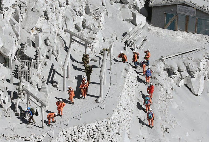 . Firefighters advance to rescue climbers near the peak of Mount Ontake in central Japan, Sunday, Sept. 28, 2014. Mount Ontake erupted shortly before noon Saturday, spewing large white plumes of gas and ash high into the sky and blanketing the surrounding area in ash. Rescue workers on Sunday found more than 30 people unconscious and believed to be dead near the peak of an erupting volcano, a Japanese police official said. (AP Photo/Kyodo News)