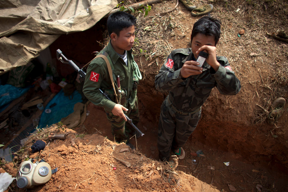 . A Kachin Independence Army (KIA) soldier uses his mobile phone while another watches as they stand near a gas mask, bottom left, in their newly-dug trench at an outpost a mile away from a hill top ceased by Myanmar\'s government troops, five miles away from the town of Laiza, in Northern Myanmar\'s Kachin-controlled region, Tuesday, Jan. 29, 2013. A key outpost protecting the headquarters of ethnic Kachin rebels in northern Myanmar has fallen to government troops, a spokesman for the guerrilla group said Sunday. The Kachin Independence Army spokesman said the hillside outpost at Hka Ya Bhum, near the guerrilla group\'s headquarters in the town of Laiza, was overrun Saturday afternoon. (AP Photo/Alexander F. Yuan)