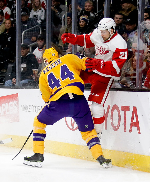 . Los Angeles Kings defenseman Robyn Regehr, left, checks Detroit Red Wings left wing Tomas Tatar during the first period of an NHL hockey game in Los Angeles, Tuesday, Feb. 24, 2015. (AP Photo/Chris Carlson)
