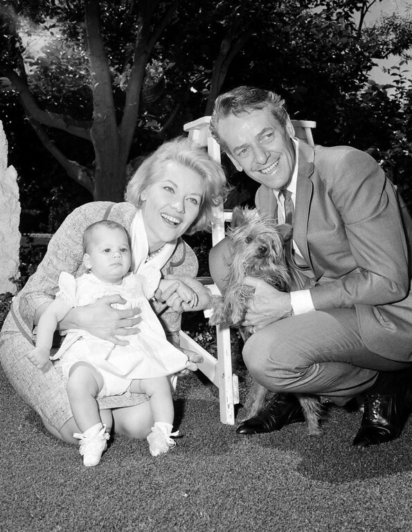 . Songstress Patti Page and her husband, Charles O\'Curran, pose with their adopted daughter, Kathleen Patricia, as the young lady makes her camera debut at the family home in Beverly Hills, Calif., May 10, 1963. Kathleen, who is 6 months old, will accompany her mother and father, a motion picture director, on their trip to the Far East later this month. Miss Page is slated for a series of singing concerts overseas. The pooch is the family\'s pet Yorkshire terrier and is named Little One. (AP Photo) No Sales