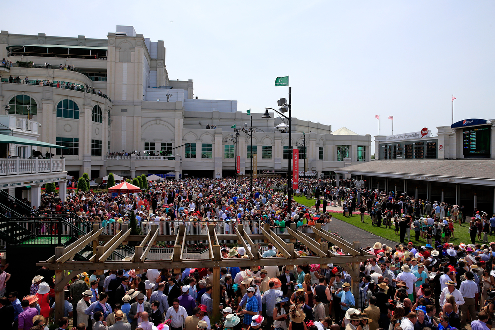 Description of . Race fans gather in the paddock prior to the 140th running of the Kentucky Derby at Churchill Downs on May 3, 2014 in Louisville, Kentucky.  (Photo by Jamie Squire/Getty Images)