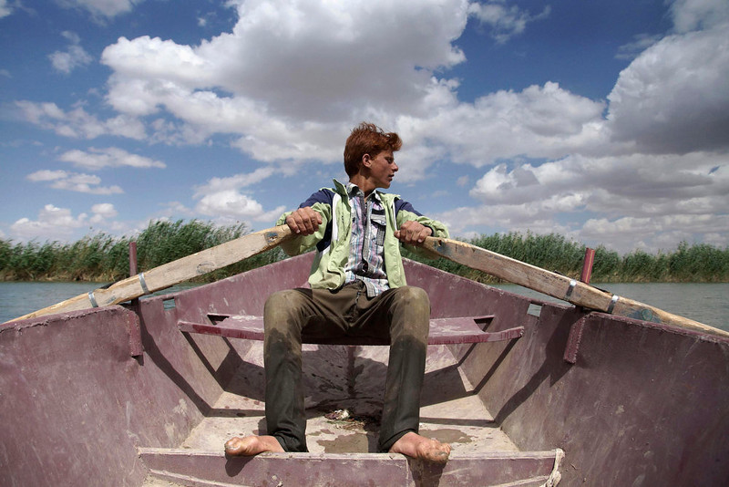 . A boy rows a boat as he transports people into the city of Deir Al-Zor April 21, 2013. Picture taken April 21, 2013. REUTERS/Khalil Ashawi