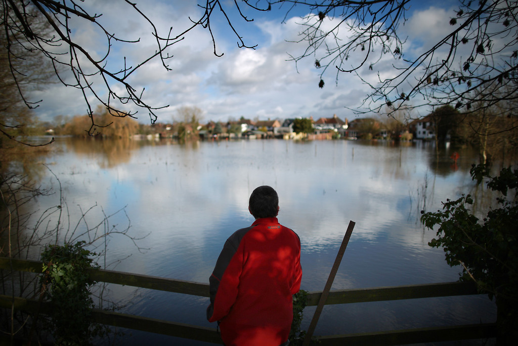 . A walker looks out at the flood waters on February 13, 2014 in Staines-Upon-Thames, England. Flood water has remained high in some areas and high winds are causing disruption to other parts of the UK with the Met Office issuing a red weather warning.  (Photo by Peter Macdiarmid/Getty Images)