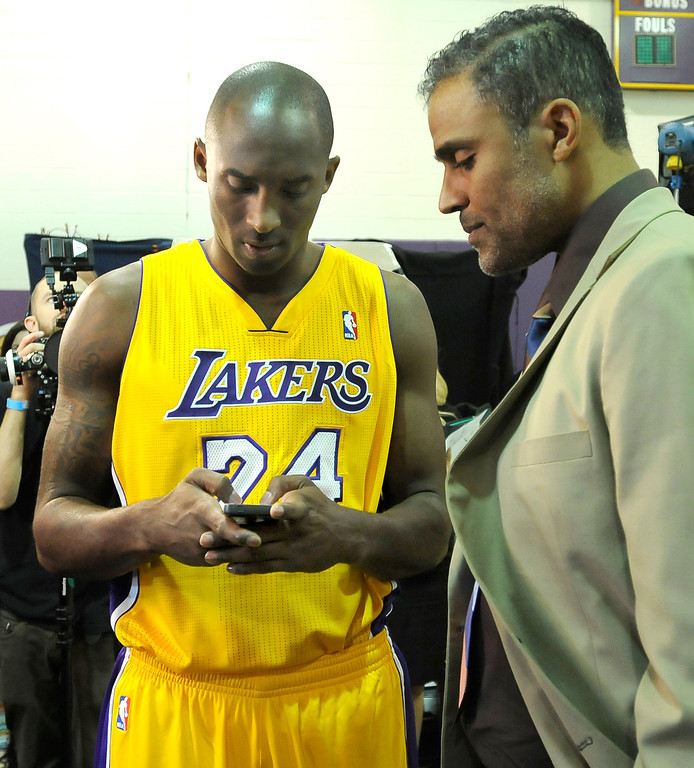 . Kobe Bryant helps his old teammate and current NBA TV reporter Rick Fox figure out his smart phone. The Los Angeles Lakers held a media day at their El Segundo practice facility. Players were photographed for team materials, and interviewed by the press. El Segundo, CA. 9/27/2013. photo by (John McCoy/Los An8eles Daily News)
