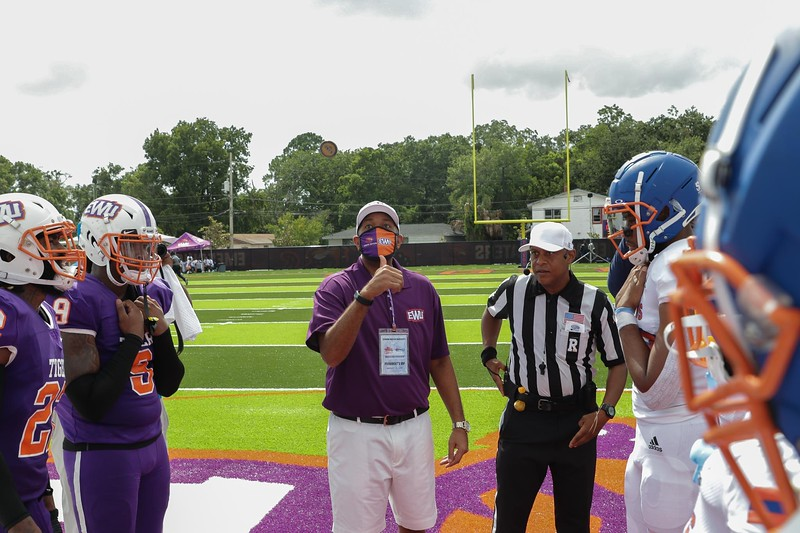 Edward Waters University president A. Zachary Faison flips a coin at midfield prior to the Tigers' first game at Nathaniel Glover Community Field & Stadium on Saturday, Aug. 28, 2021.