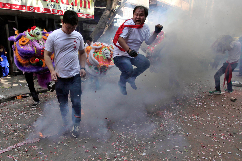 . A Chinese youth of Indian origin jumps over exploding fire crackers during Chinese New Year celebrations in Kolkata, India, Friday, Jan. 31, 2014. (AP Photo/Bikas Das)