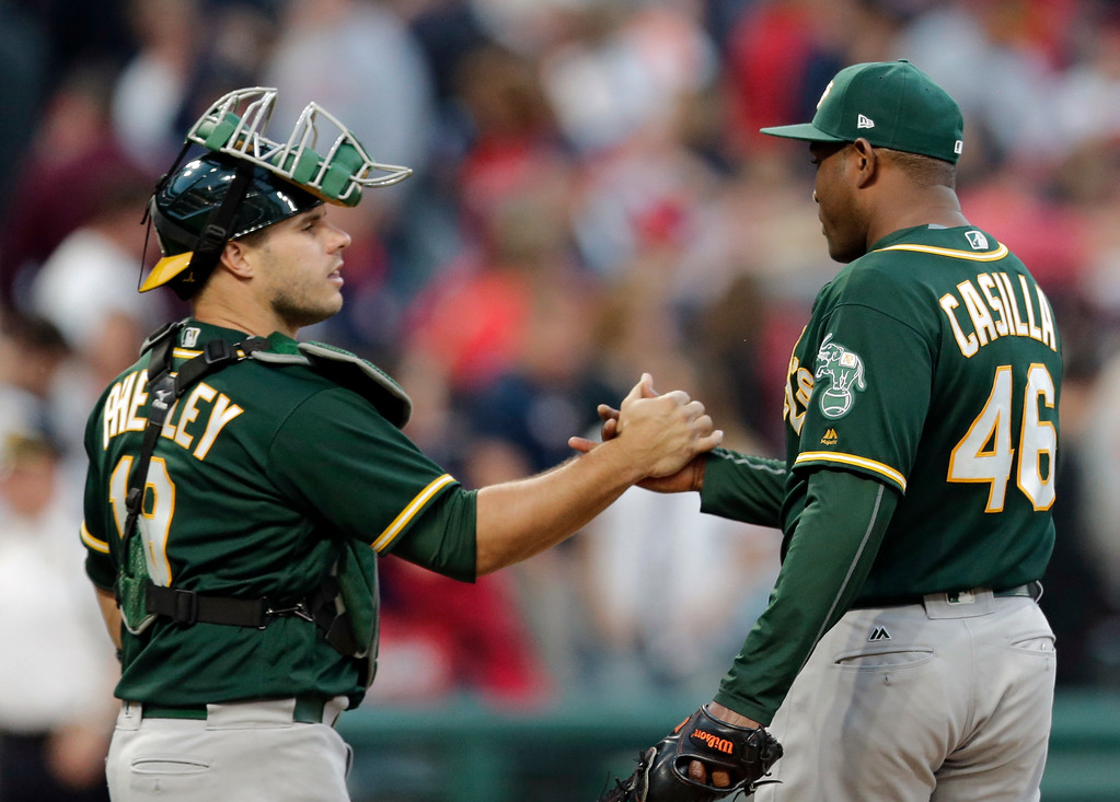 . Oakland Athletics relief pitcher Santiago Casilla, right, is congratulated by catcher Stephen Vogt after the Athletics defeated the Cleveland Indians 3-1 in a baseball game, Wednesday, May 31, 2017, in Cleveland. (AP Photo/Tony Dejak)
