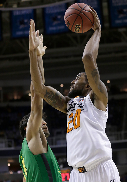 . Oklahoma State forward Michael Cobbins (20) shoots over Oregon forward Arsalan Kazemi (14) during the first half of a second-round game in the NCAA college basketball tournament in San Jose, Calif., Thursday, March 21, 2013. (AP Photo/Jeff Chiu)