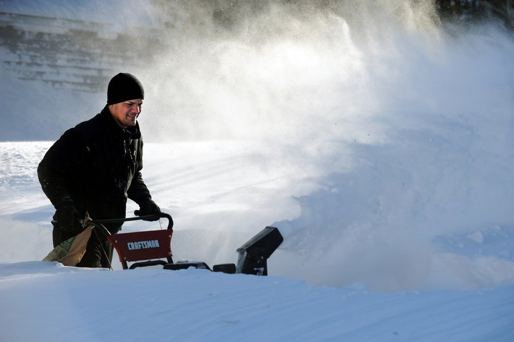 Description of . Tony Colon uses a snowblower to clear his driveway in Derby, Conn., as residents face massive snow removal, Saturday, Feb. 9, 2013, following a severe blizzard that dumped up to three feet of snow across the state. (AP Photo/The Connecticut Post, Autumn Driscoll)