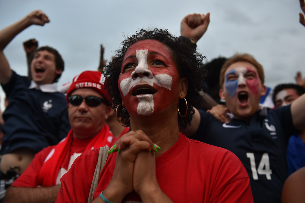 . Swiss supporters are surrounded by cheering French supporters who celebrate a goal as they watch a live telecast in Rio de Janeiro on June 20, 2014, of the Group E football match between Switzerland and France at the Fonte Nova Arena in Salvador, during the 2014 FIFA World Cup. YASUYOSHI CHIBA/AFP/Getty Images