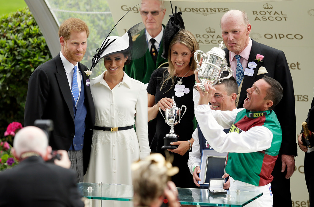 . Britain\'s Prince Harry and Meghan, Duchess of Sussex present the trophy for the St James\'s Palace Stakes to Frankie Dettori, right, on the first day of the Royal Ascot horse race meeting in Ascot, England, Tuesday, June 19, 2018. (AP Photo/Tim Ireland)