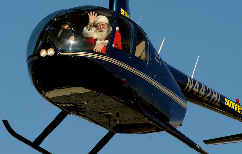 """. Santa arrives for a visit to Lupita\'s Restaurant in Aurora, CO, Saturday December 18, 2010. Santa Claus was flown to the restaurant in a helicopter, by Rotors of the Rockies for the 5th year. Owner Betty Oxley has been throwing a Christmas celebration for area children for 16 years. She says it started with Santa coming and sitting on the floor with children and has grown considerably over the years. She said, \""""One day I was talking with a friend of mine, Bill, he\'s a pilot. I said it would be nice to bring Santa in on a helicopter. Don\'t you have connections?\"""" Bill Totten put Betty in touch with Rotors of the Rockies. She continues, \""""They never charged me a dime- they will not take anything. They\'re wonderful people.\""""  (Craig F. Walker/ The Denver Post)"""