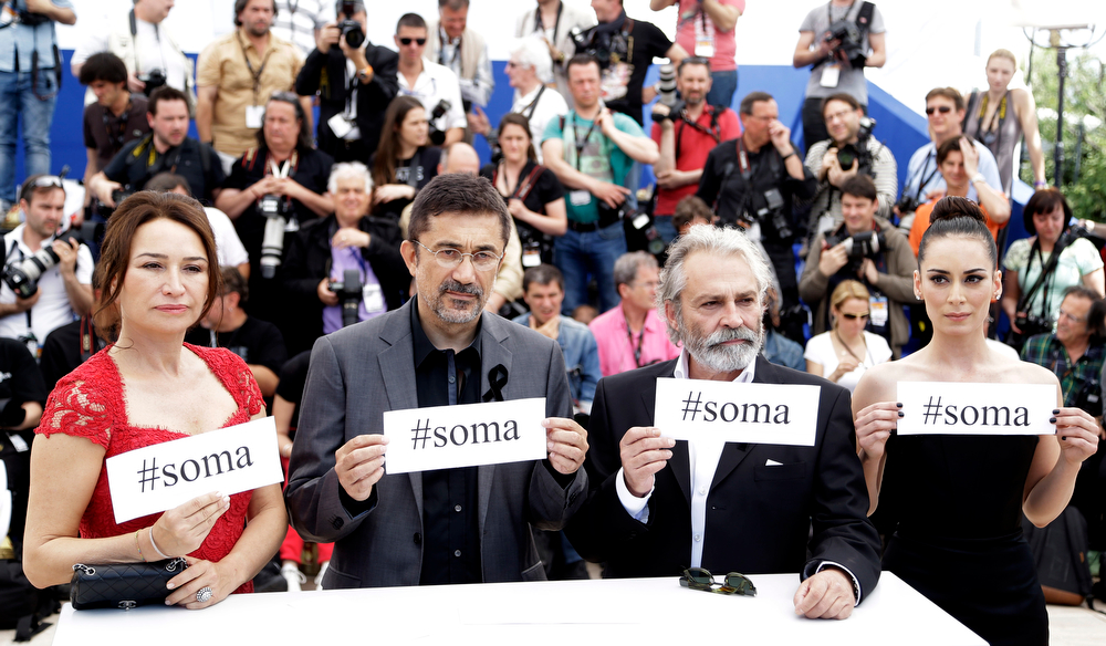 ". From left, actress Demet Akbag, director Nuri Bilgle Ceylan, actor Haluk Bilginer and actress Melisa Soezen pose for photographers with signs reading ""soma\"", a reference to Turkey\'s worst mining incident in which hundreds of miners were killed earlier this week in Soma, Turkey, during a photo call for Winter Sleep at the 67th international film festival, Cannes, southern France, Friday, May 16, 2014. At least 250 people died in a coal mine explosion and fire, which has set off a raft of protests and public outrage at allegedly poor safety conditions at Turkish coal mines, widespread corruption and what some perceived as government indifference.  (AP Photo/Thibault Camus)"