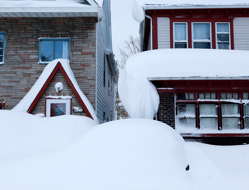 . Snow is piled high on a vehicle and on houses in the south Buffalo area on Thursday, Nov. 20, 2014, in Buffalo, N.Y. A new blast of lake-effect snow pounded Buffalo for a third day piling more misery on a city already buried by an epic, deadly snowfall that could leave some areas with nearly 8 feet of snow on the ground when it\'s all done. (AP Photo/Mike Groll)