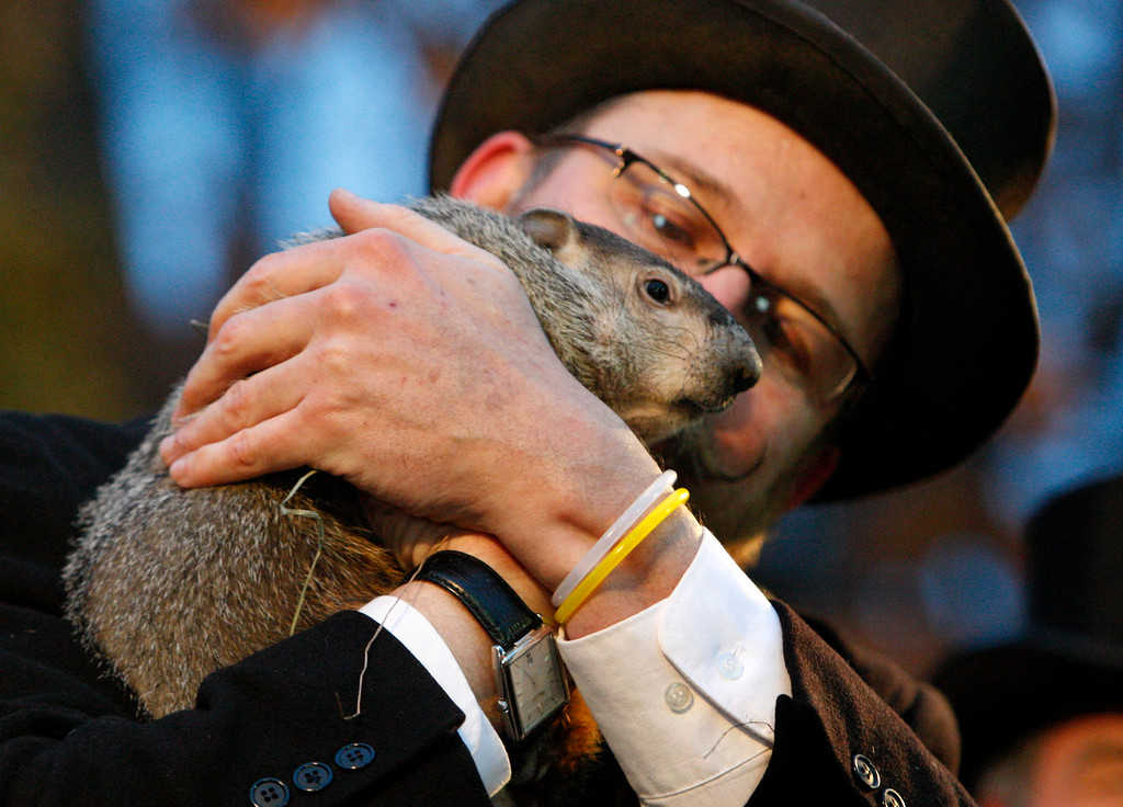 . Punxsutawney Phil, right, is held by Ben Hughes after emerging from his burrow on Gobblers Knob in Punxsutawney, Pa., to see his shadow and forecast six more weeks of winter weather Tuesday, Feb. 2, 2010.  (AP Photo/Gene J. Puskar)