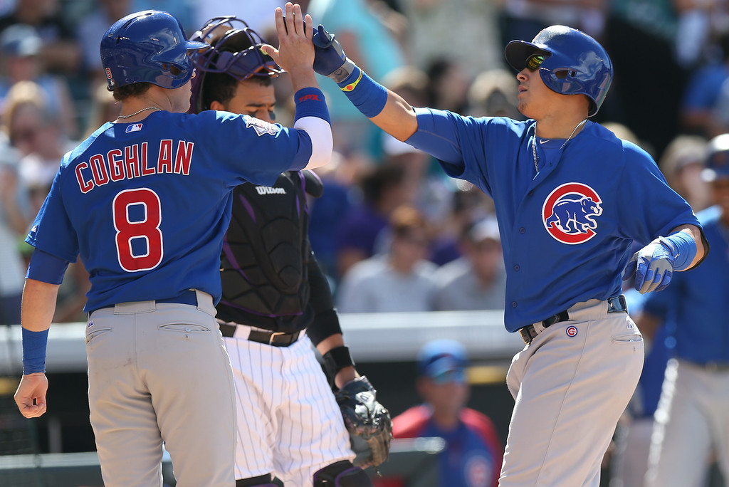 . Chicago Cubs\' Chris Coghlan, front left, congratulates teammate Javier Baez, front right, as he crosses home plate after hitting a two-run home run against the Colorado Rockies in the eighth inning of the Cubs\' 6-2 victory in a baseball game in Denver on Thursday, Aug. 7, 2014. Rockies catcher Wilin Rosario, back, looks on. (AP Photo/David Zalubowski)