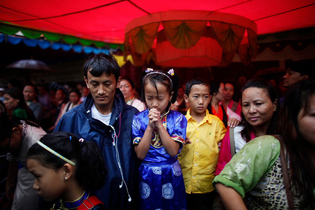 . A young Tibetan girl offers prayers during celebrations to mark the birthday of their spiritual leader the Dalai Lama in Katmandu, Nepal, Saturday, July 6, 2013. The Tibetan leader turned 78 today. (AP Photo/Niranjan Shrestha)
