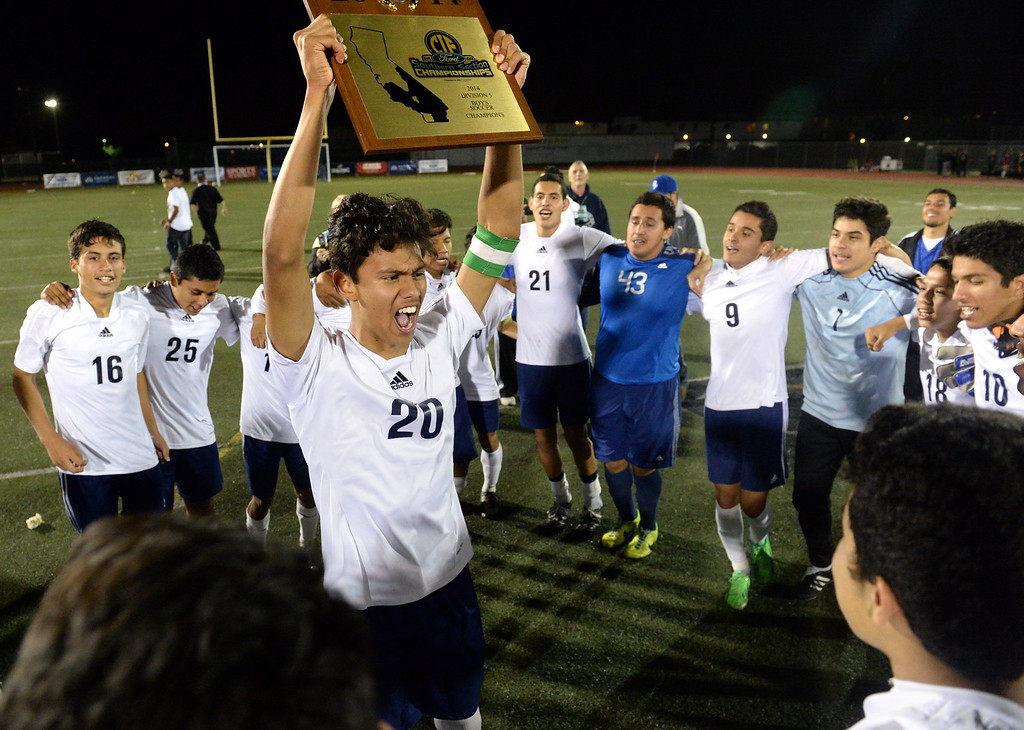 . Baldwin Park\'s Danny Vega hoists the Championship Plaque after defeating Marshall in their CIF-SS Division 5 boys soccer game at Warren High School in Downey on Friday March 7, 2014. Baldwin Park defeated Marshall 5-4 in penalty kicks after scoring 0-0 in overtime. (Staff Photo by Keith Durflinger/San Gabriel Valley Tribune)