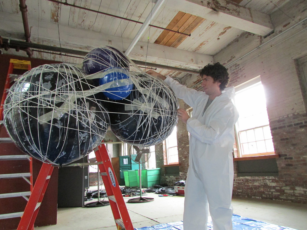 ". On Tuesday, Wilco\'s Lighting and Visual Production Designer Jeremy Roth works on a ""string cloud\"" that will hold lights during Wilco\'s concerts at Solid Sound Festival 2013. The string cloud lights will be exclusive to the festival. (Jennifer Huberdeau/North Adams Transcript)"