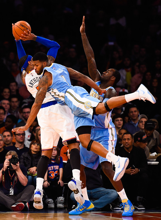 . NEW YORK, NY - NOVEMBER 16: Carmelo Anthony #7 of the New York Knicks shoots over J.J. Hickson #7 and Alonzo Gee #1 of the Denver Nuggets in the first half at Madison Square Garden on November 16, 2014 in New York City. NOTE TO USER: User expressly acknowledges and agrees that, by downloading and/or using this photograph, user is consenting to the terms and conditions of the Getty Images License Agreement.  (Photo by Alex Goodlett/Getty Images)